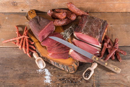 Smoked meats and sausages on wooden background