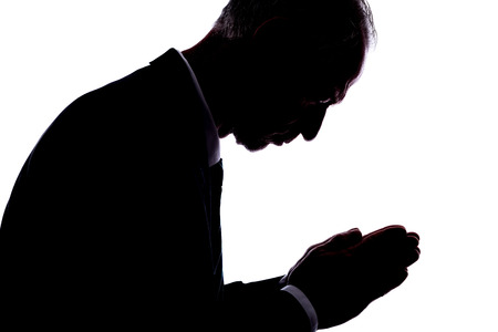 expressing: Silhouette of a man expressing prayer Stock Photo