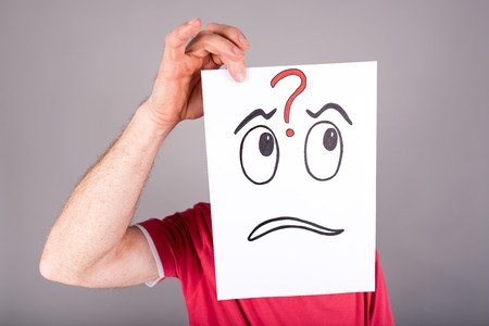 interrogative: Hombre que sostiene un papel con una cara con una expresi�n interrogante