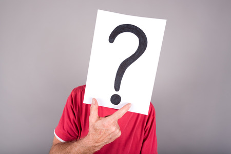 embarassed: Man behind a paper with a question mark