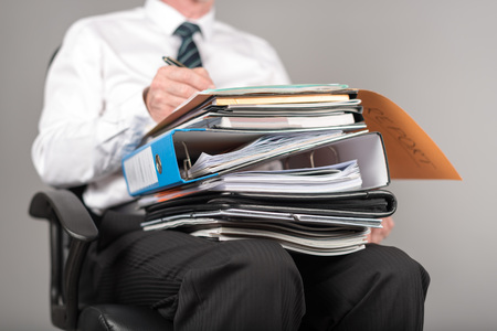 job deadline: Businessman working with folders on his knees, on grey background Stock Photo