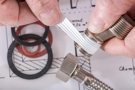 fontanero: Plomero poner una junta de tefl�n en un hilo, de cerca Foto de archivo
