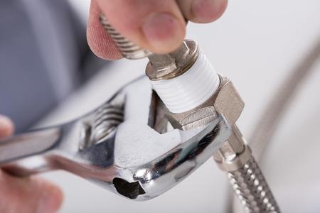 Plumber screwing plumbing fittings, closeup Archivio Fotografico