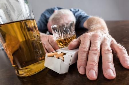 borracho: Hombre borracho se desplomó sobre la mesa después del abuso de alcohol