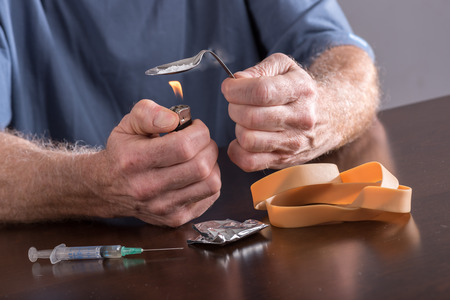 drug overdose: Drug addict preparing a dose of heroin Stock Photo