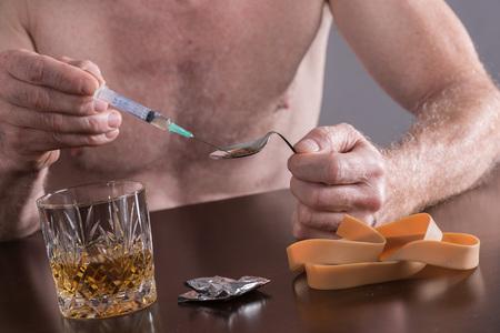 heroin: Drug addict preparing a dose of heroin Stock Photo