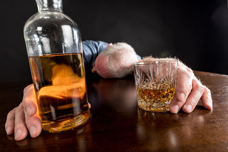 alcohol bottle: Drunk man slumped on table after alcohol abuse
