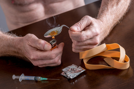 illegal drugs: Drug addict preparing a dose of heroin Stock Photo