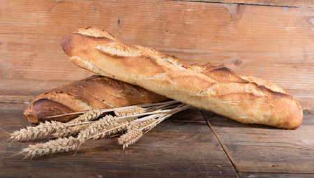 crust crusty: Crusty fresh baguettes on wooden background Stock Photo