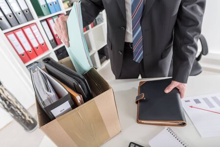 Businessman fired, putting his personal effects in a box