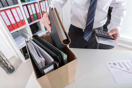 layoff: Businessman fired, putting his personal effects in a box