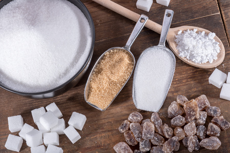 sugar cubes: Composition of different types of sugar, on wooden background