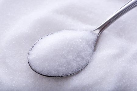 cuchara: Cucharadas de azúcar blanco cristal en el fondo de azúcar