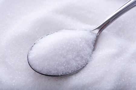 spoon: Spoonfuls of crystal white sugar on sugar background