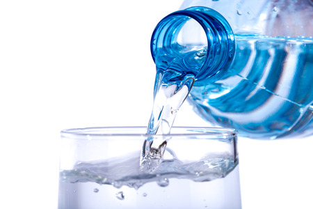 Water poured from a plastic bottle into a glass, isolated on white Stock Photo