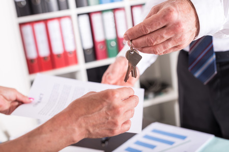 agency agreement: Realtor giving house keys to his client after signing the contract