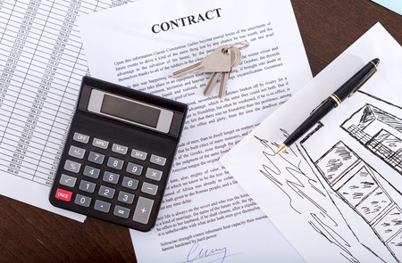 key signature: Real estate contract with keys, calculator and pen (random english dummy text used)
