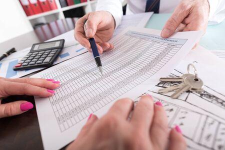 Estate agent showing a financial plan to his customer Foto de archivo