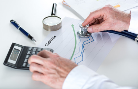 healthy economy: Businessman holding a stethoscope on a graph showing growth