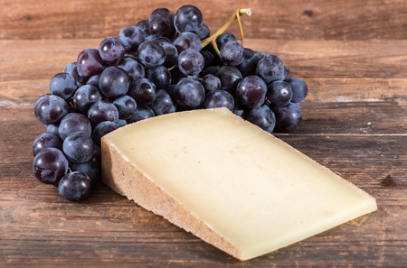French Comte cheese with black grapes on wooden background county