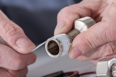 plumber: Plomero poner una junta de teflón en un hilo, de cerca Foto de archivo