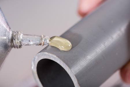 fontanero: Plomero poniendo pegamento en un tubo de pvc, primer