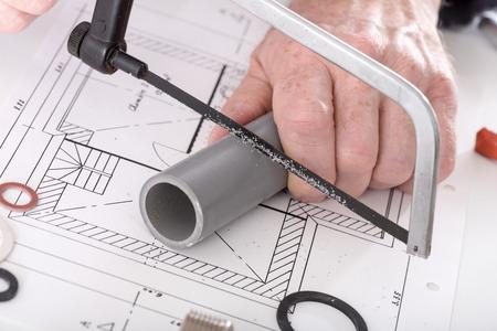 kunststoff rohr: Plumber Sägen ein PVC-Rohr auf einem Plan Lizenzfreie Bilder