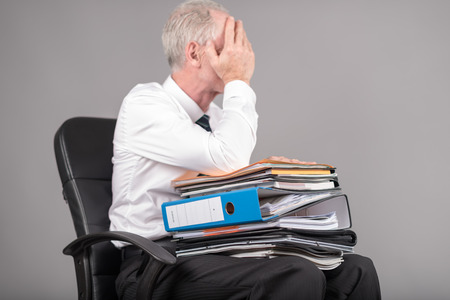 overburdened: Businessman overloaded holding his face with his hands