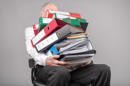 overburdened: Businessman overloaded carrying a pile of binders and folders