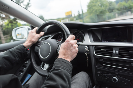 car dashboard: Car driving with both hands on the wheel