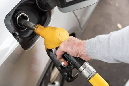 fueling: Hand holding yellow fuel pump nozzle and refilling car Stock Photo