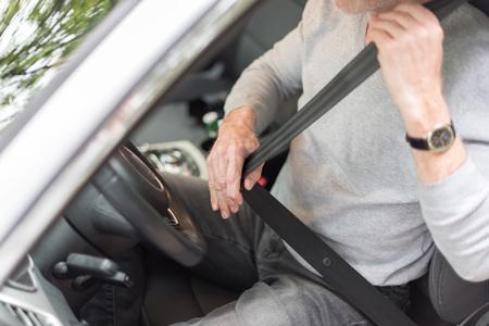fastening: Man fastening seat belt in car