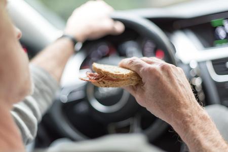 Man eet een broodje tijdens het rijden