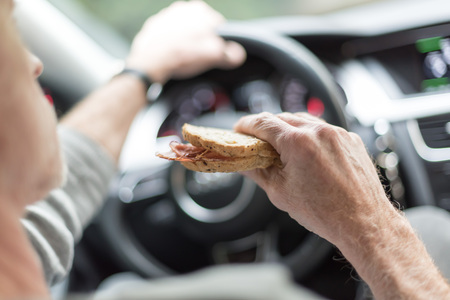 Man eating a sandwich while driving