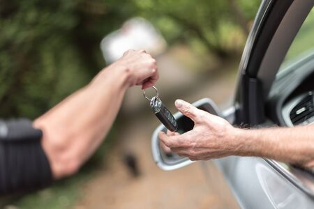 key handover: Woman handing another person automobile keys Stock Photo