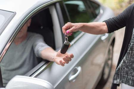 handover: Woman handing another person automobile keys Stock Photo