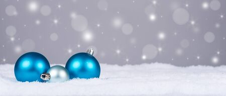 winter card: Christmas balls in snow with sparkle background