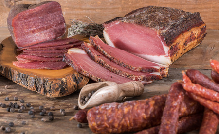 eating meat: Smoked meats and sausages on wooden background