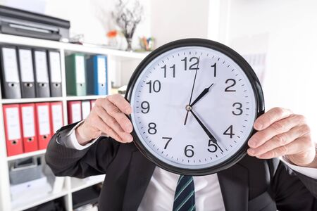 job deadline: Businessman holding a clock in front of his head