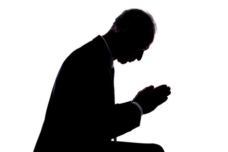 black hands: Silhouette of a man expressing prayer Stock Photo
