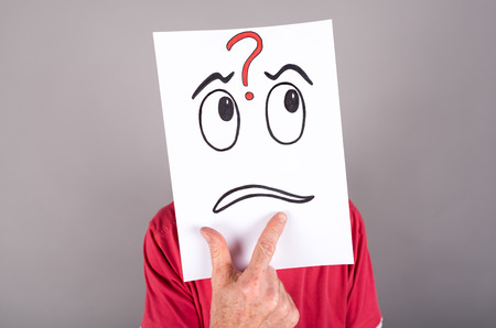 embarassed: Man behind a paper with a questioning expression