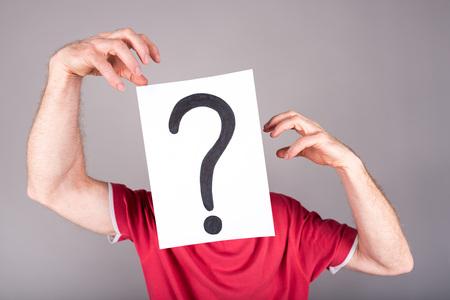 interrogativa: El hombre detr�s de un papel con un signo de interrogaci�n