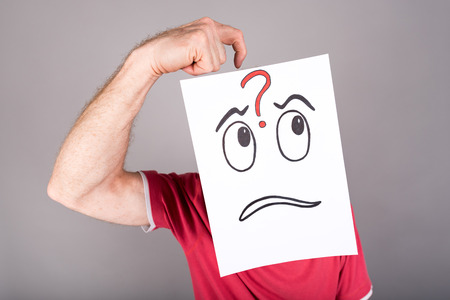 interrogative: Man behind a paper with a questioning expression