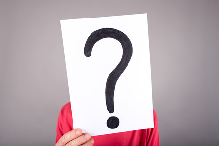 signo de interrogación: Hombre que sostiene un papel con un signo de interrogación Foto de archivo
