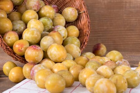 canastas con frutas: mirabelles frescas con cesta en una toalla