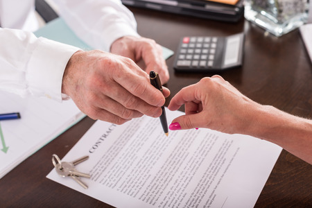 business contract: Realtor giving his client a pen to sign the contract
