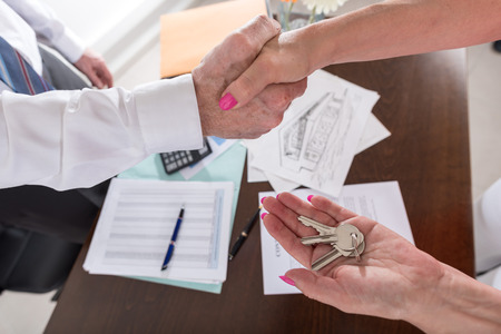 mortgage: Estate agent shaking hand with female customer Stock Photo