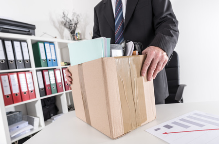 Businessman fired, leaving his office with his personal effects Archivio Fotografico