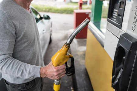 nozzle: Man holding a yellow fuel pump nozzle