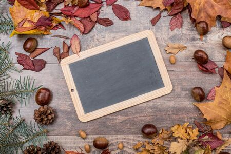 bordered: Slate on wooden background bordered with leaves and chestnuts